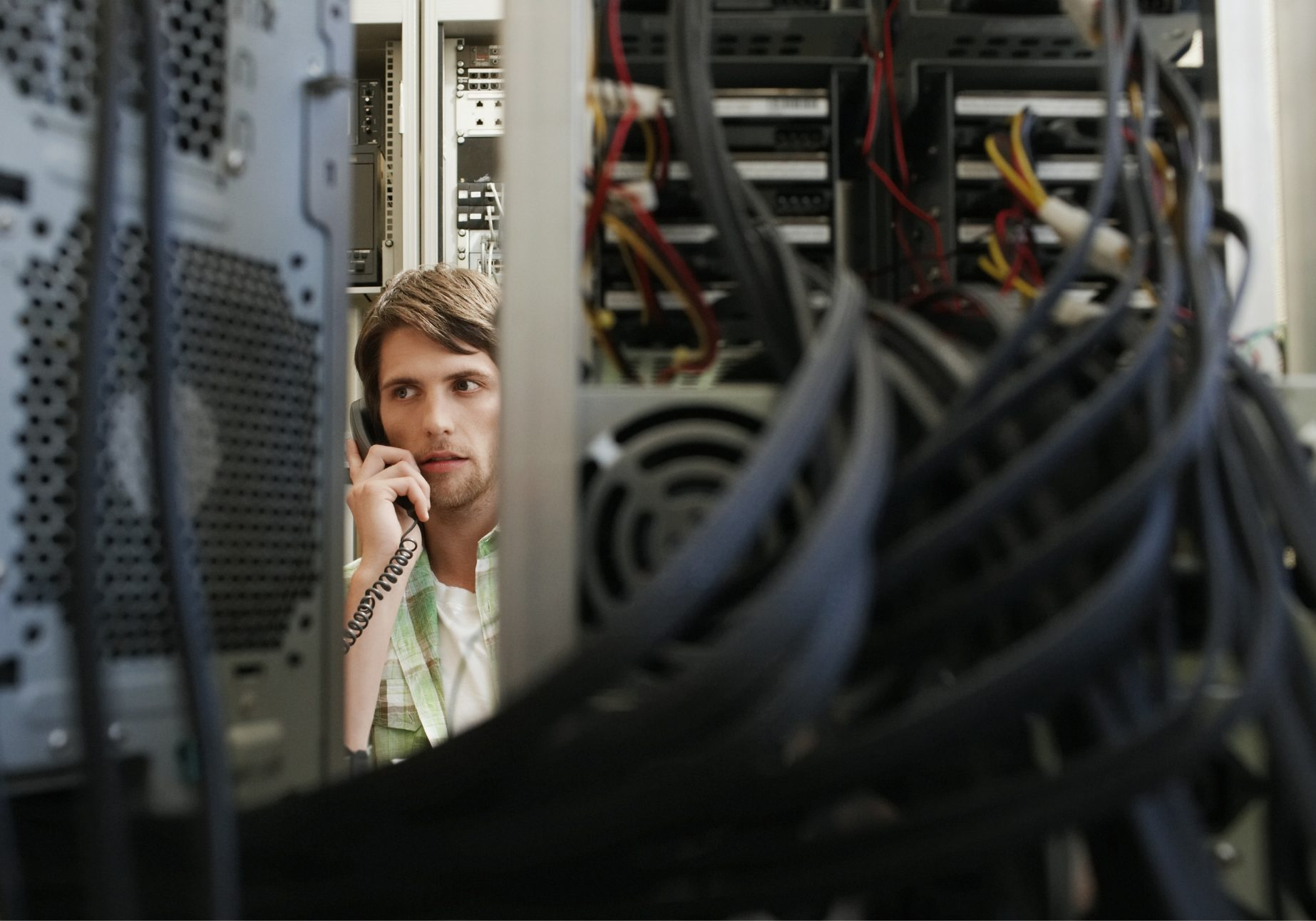 man looking at IT Servers and making a call